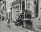 Ongelokaliseerd, krantenlezende man op stoep, meisje op autoped in de straat