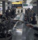 Wachtende passagiers bij een bagageband in de bagagereclaimhal van Schiphol