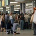Afhalers wachtend op aankomende passagiers in aankomsthal 1 van Schiphol