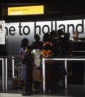 Passagiers voor de paspoortcontrolebalie tegenover de E-pier op Schiphol met een…