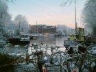Realengracht met een sleepboot en woonschepen in wintertooi gezien in zuidwestel…