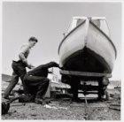 Mannen schilderen onderkant bootje aan de Oosterringdijk