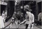 Rugzaktoeristen in de Sint Annenstraat. Op de voorgond passanten in de Warmoesst…