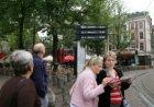 Reizigers op een tramhalte op het Leidseplein met display met digitale informati…
