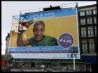 Prins Hendrikkade 90 t/m 93 met een metershoog geveldoek bedrukt met reclame aan…