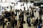 Passagiers en wegbrengers bij de incheckbalies in de vertrekhal