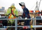 Bouwput voor de aanleg van de Noord/Zuid-metrolijn aan de IJ-oevers. Bouwvakkers…