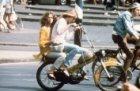 Straatbeeld - jongen en meisje op gele brommer