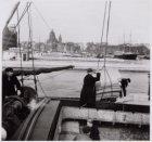 Oosterdok met het laden of lossen van een binnenvaartschip gezien in noordwestel…