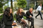 Drie jonge vrouwen tijdens een lunch op een van de plantenbakken op het Zuidplei…