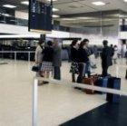 Wachtende passagiers en wegbrengers in vertrekhal 2 van Schiphol