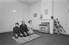 Portret van een biddend gezin met een Indiase vader