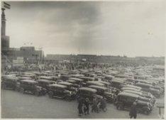 Geparkeerde auto's en autobussen en een mensenmenigte op het Stadionplein in ver…