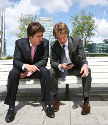 Jonge mannen laten elkaar op het Gustav Mahlerplein spelletjes zien op hun mobieltjes