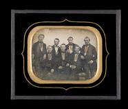 Visualizza Gruppebilde med syv unge menn, tre av dem sit… anteprime su