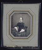 Thumbnail af Junge Frau auf einem Stuhl an einem Tisch sit…