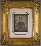 Thumbnail preview of Halbporträt einer Frau neben einem Tisch mit …