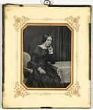 Thumbnail af Junge Frau am Tisch sitzend, einen Arm aufges…