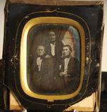 Visualizza Tre menn, gruppebilde. To sitter og en står m… anteprime su