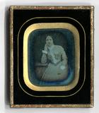 Visualizza Ein Frau mittleren Alters sitzt an einem klei… anteprime su