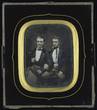 Prévisualisation de Zwei junge Männer nebeneinander sitzend, den … imagettes