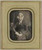 Thumbnail preview van Ältere Frau mit weißer Haube in dunklem Kleid…