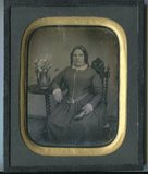 Visualizza Seated woman holding a book. Flowers in a vas… anteprime su
