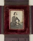 Visualizza Portrait of a woman in polka-dot dress, seate… anteprime su
