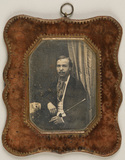 Visualizza Portrait of a man with moustache, seated, hol… anteprime su