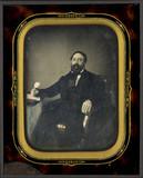 Visualizza Portrait d'homme barbu, à-mi-jambes, assis, d… anteprime su