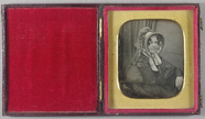Thumbnail af Half-length portrait of a seated woman on a c…