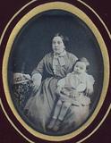 Visualizza Jeune femme tenant son enfant sur ses genoux anteprime su