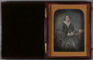 Visualizza Portrait, three quarter length of a seated wo… anteprime su