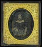 Esikatselunkuvan Junge Frau an einem Tisch sitzend, auf dem ei… näyttö