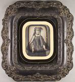 Thumbnail af Knieporträt einer jungen Frau mit Hut.