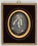 Visualizza Frau mit einer weißen Haube an einem Tisch si… anteprime su