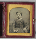 Miniaturansicht Vorschau von Half length portrait of a seated boy. He has …