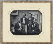 Visualizza Vier junge Männer vor einer Hauswand und Tür … anteprime su