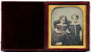 Thumbnail preview of Portrait of two children, one seated in a cha…
