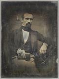 Esikatselunkuvan Mann mit einem Buch in der Hand am Tisch sitz… näyttö