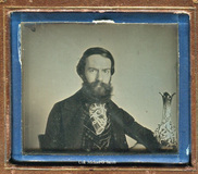 Visualizza Portrait of young bearded man seated at table… anteprime su