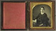 Visualizza Junge Frau mit langer Kette sitzt neben einem… anteprime su