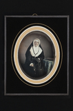 Visualizza Portrait of a nun, sitting near a table with … anteprime su