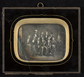 Thumbnail preview of Group portrait of 10 young men in studio. Dra…