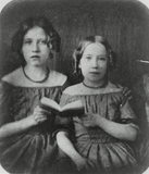 Visualizza portrait of two seated girls holding a book t… anteprime su