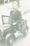 De jonge Wim Maarseveen in zijn speelgoedauto in d...
