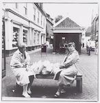 Twee dames met boodschappentassen op een bankje in...