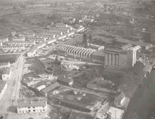 Luchtfoto van het terrein tussen Grote Koppel (rechts) en Hooglandseweg (achtergrond, links). Links in beeld de Koppelweg, die door het nieuwbouwwijkje Jeruzalem voert. Rechts de Cova; er wordt juist een nieuwe fabriekshal gebouwd.