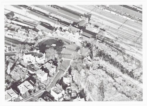 Luchtfoto van het station met spoorweg emplacement en een deel van de Berg. Op de voorgrond een deel van de Regentesselaan en de Koningin Wilhelminalaan.
