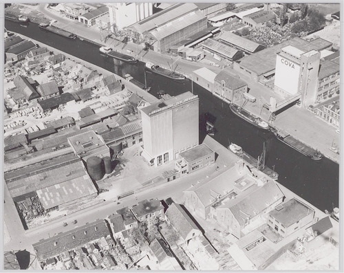 Luchtfoto van het havengebied ter hoogte van de silo's van Cova en Nieuwenhuizen. Op de voorgrond de Eemstraat, de Kleine Koppel en de buurt het Sasje. Rechtsboven de Grote Koppel.